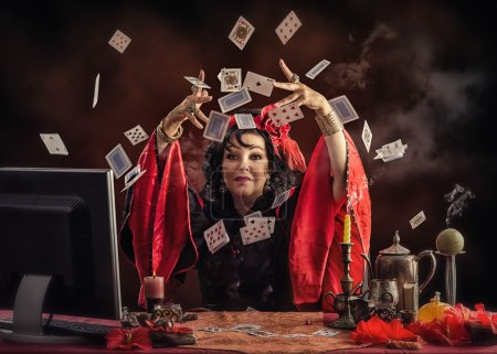 Photo for Mature Gypsy seer is tossing up playing cards to predict future her online customer. Black-haired woman wears red-black blouse sitting at the desk with smoking candles and other occult items - Royalty Free Image