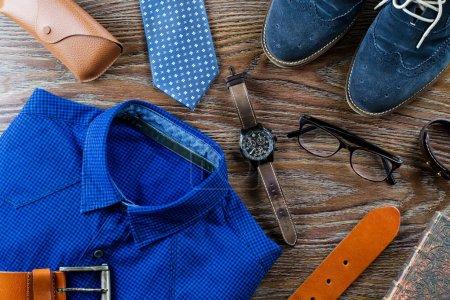 Vêtements et accessoires homme élégant plat couché dans des couleurs bleues et brunes sur un fond en bois