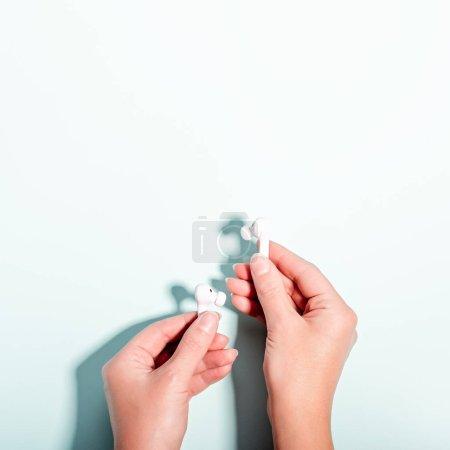 Photo pour Écouteurs sans fil blancs à la main féminine sur fond pastel, espace de copie. Technologie moderne couché plat avec écouteurs sans fil dans la main de la femme, concept de style de vie moderne, vue de dessus - image libre de droit
