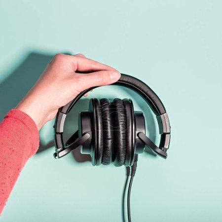 Photo pour Casques massifs noirs à la main féminine sur fond pastel, espace de copie. Technologie moderne couché plat avec écouteurs sur-oreille dans la main de la femme, concept de style de vie moderne, vue de dessus - image libre de droit