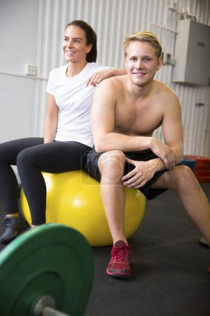 Confident Athletes Sitting On Exercise Ball In Health Club