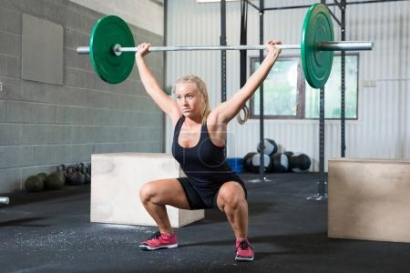 Determined Woman Lifting Weights In Health Club
