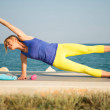 Young athletic woman exercising outdoors: side pla...
