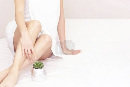 Concept of smooth beautiful skin without extra hair. A beautiful girl sits and looks at a cactus. depilation. no to hair. copyspace. place your text
