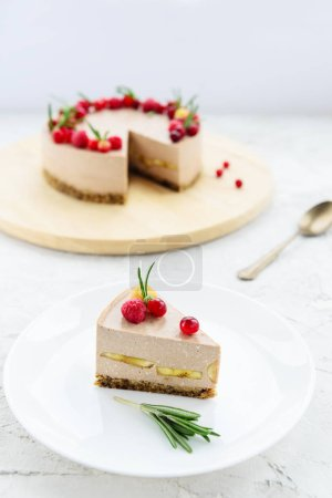 Photo for Slice of raw cheesecake with cocoa, banana and berries on a white plate. Gluten free, vegetarian food. - Royalty Free Image