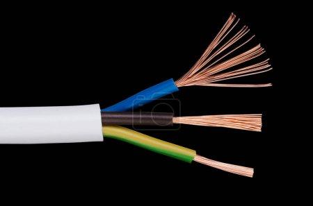 Photo pour Câble d'alimentation électrique Iec standard sur fond noir. Coupe transversale. Gaine de câble, isolants en marron, bleu et jaune-vert avec des fils de cuivre tressés flexibles. Macro gros plan photo. - image libre de droit