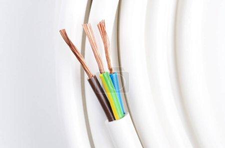 Photo pour Câble électrique avec trois conducteurs isolés. Section de câble d'alimentation. Gaine de câble avec l'isolation des fils et des fils de cuivre multibrins souples. Code de couleur standard IEC. Photo macro d'avove. - image libre de droit