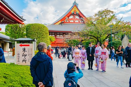 Photo for Tokyo. Japan. Asakusa Temple. Tourist is photographed with girls in national costumes. Tourism in Japan. Tourists near Asakusa Temple. Walk around Tokyo. Buddhist temple in Tokyo. 11.09.2019 - Royalty Free Image
