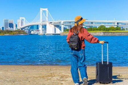 Photo for Odaiba island. Japan. Rainbow Bridge in Tokyo.  bridges in Japan. Woman is traveling. Suspension bridge. North Tokyo Bay. Japan on a sunny day. A girl with a suitcase is standing on the beach. - Royalty Free Image