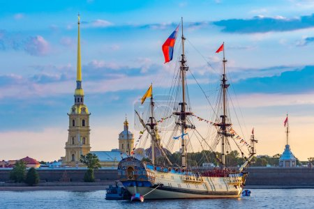 Photo for Saint Petersburg. Sailboat with flags on the background of the Peter and Paul fortress. A Brigantine with lowered sails is moored on the Neva. Rivers Of St. Petersburg. Early morning in Petersburg. - Royalty Free Image