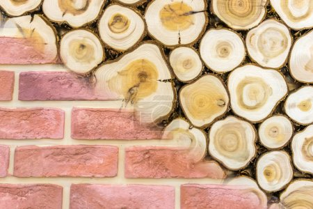 Photo for Comparison of wood and brick. Tree trunks next to a brick wall. Concept- the choice of material for building a house. Wooden beams. Concept- building materials store. Selection of building materials - Royalty Free Image
