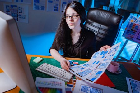 Photo for App design. Business woman holds paper with mockups of mobile applications. Mobile site templates on paper. Woman compares layouts on paper with a monitor. Mobile application development. - Royalty Free Image