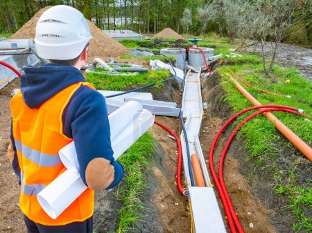 Photo for Laying utilities. Man looks at the pipes leading to the well. Builder with drawings next to the water supply. Pipes at the construction site lead. Human in a construction uniform looks at water pipes - Royalty Free Image