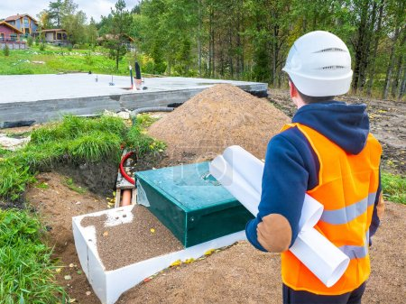 Photo for Septic tank near the foundation. Autonomous conolization. Builder is looking at a septic tank. Treatment facilities at a construction site. Team leader will check the correct septic tank. - Royalty Free Image