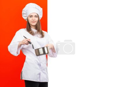 Photo for Cook girl. A girl in a chef's uniform on a red and white background. Place for text. A woman cook with a ladle in her hand. The girl in the chef's hat. Food preparation. Cooking. Restaurant. - Royalty Free Image