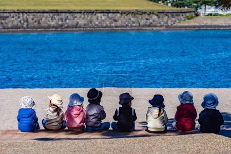 Photo for Small children sit on the shore and look at the water. Kids sitting by the river. Kids in Panama hats removed from the back. Small children on the background of water. Kindergarten. - Royalty Free Image