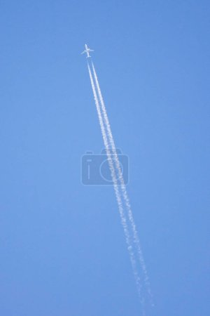 Photo for Passenger airplane at cruising altitude against blue sky. - Royalty Free Image