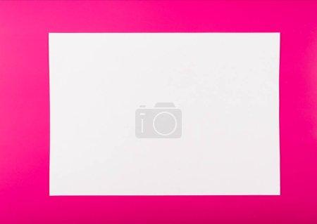Foto de Una hoja de papel de oficina blanca sobre un fondo sólido de color rosa - Imagen libre de derechos