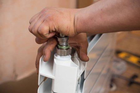 Photo pour Remplacement du radiateur dans l'appartement, travaux de plomberie. Un homme effectue le montage de la batterie de chauffage. - image libre de droit