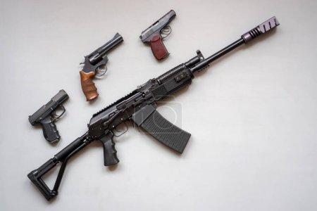 Photo pour Gros plan d'une mitrailleuse à sanglier et d'un pistolet sur fond gris. Isolé. pose plate - image libre de droit