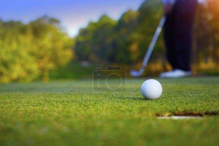 Verschwommener Golfer beim Golfen am Abend auf dem Golfplatz, in der Sonne