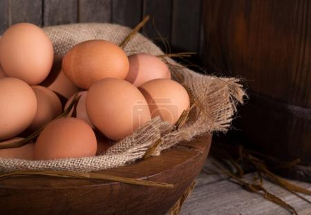 Photo for Closeup of brown chicken eggs in a wooden bowl with a rustic background - Royalty Free Image