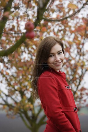 woman in red coat under apple tree