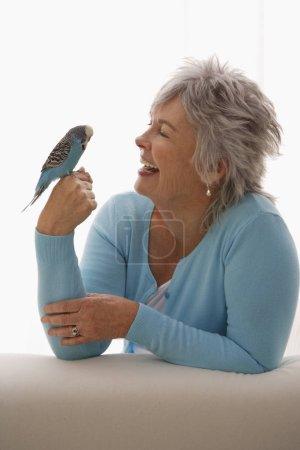 Older woman holding blue bird