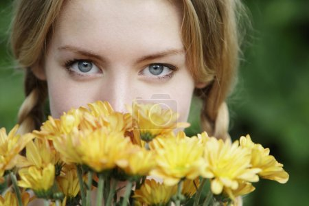 Photo for Close up of young woman with flowers in front of her face - Royalty Free Image