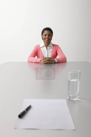 young woman sitting on end of the table
