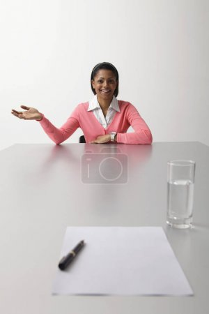 Young woman sitting at end of table