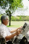 Senior man reading newspaper in park