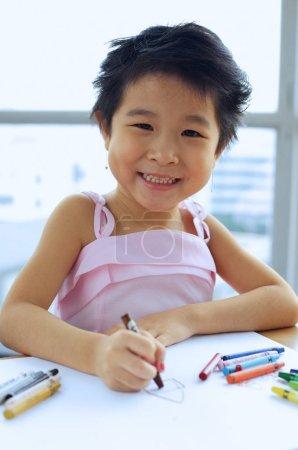 Photo pour Jeune fille avec des crayons, souriant à la caméra - image libre de droit