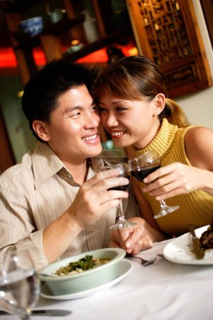 Couple in restaurant, sitting cheek to cheek