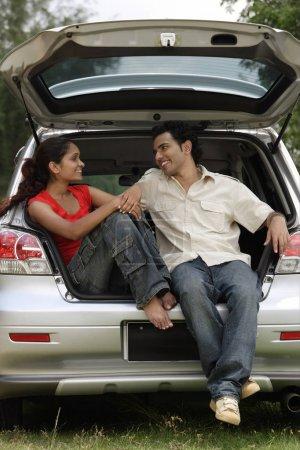 Photo pour Jeune couple assis dans le coffre de la voiture - image libre de droit