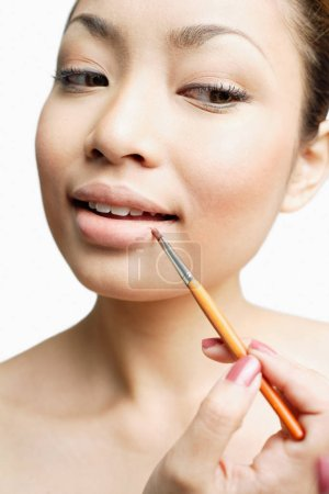 woman using lipstick brush