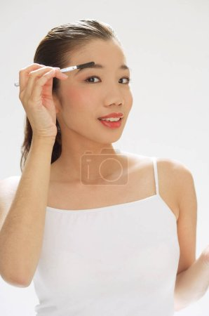 Woman holding brush to eyebrows