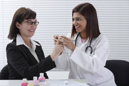 Doctor applying bandage to patient's finger