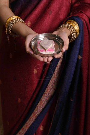 Indian woman offering sweets