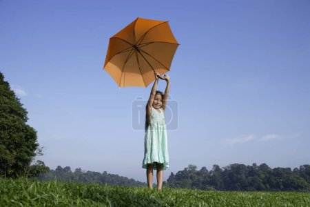 Photo for Little girl in dress holding umbrella in green meadow - Royalty Free Image