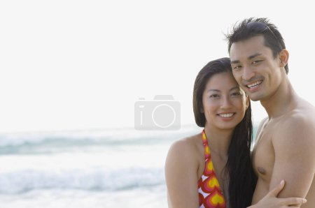 Couple looking at camera, sea behind them...
