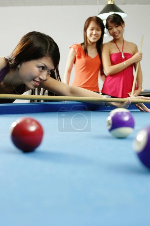 Woman holding pool cue aiming