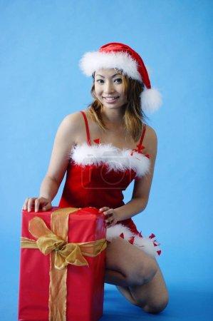 Photo pour Femme dans le chapeau de Père Noël, accroupi à côté de la boîte cadeau - image libre de droit