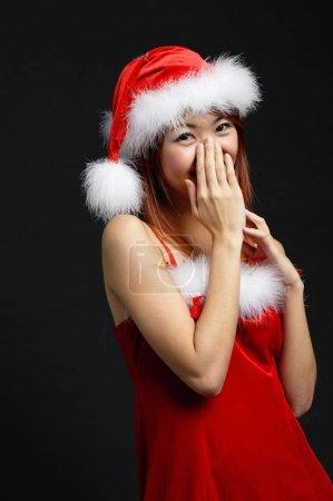 Photo pour Femme portant un chapeau de Père Noël et une robe rouge, couvrant la bouche à la main - image libre de droit