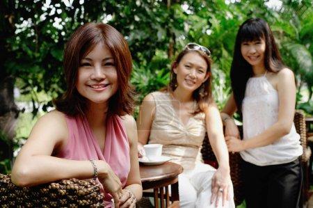 Photo pour Trois femmes au café jardin en plein air, souriant à la caméra, portrait - image libre de droit