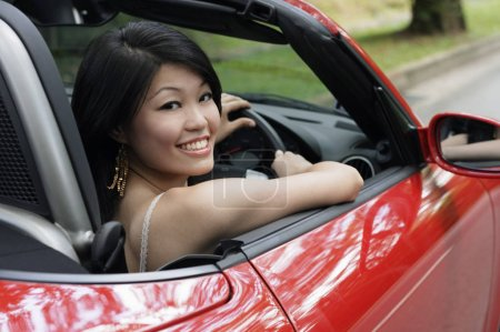 Woman in red sports car