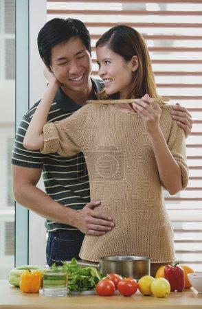 Man embracing woman from behind, woman feeding man