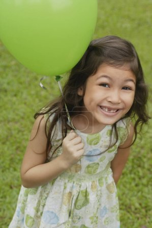Photo pour Jeune fille tenant le ballon sur l'herbe verte - image libre de droit
