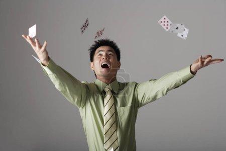 man throwing cards up