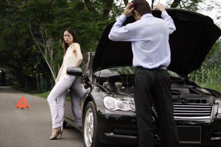Man looking under car hood of broken down car
